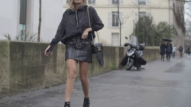 A guest wears a silver jacket black shoes with star print a black leather top and a black leather skirt outside the Valentin Yudashkin show during...