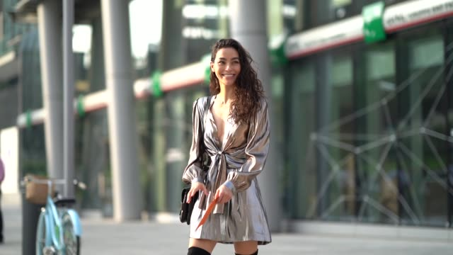 a guest wears a silver low neck shiny dress a bag black thigh high boots outside the alberta ferretti show during milan fashion week spring/summer... - spring summer collection stock videos & royalty-free footage
