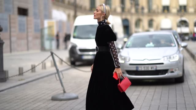 guest wears a studded headband, a black velvet dress with puff sleeves, a transparent black hi-neck top with white pattern print, a large black belt... - fashion week stock videos & royalty-free footage