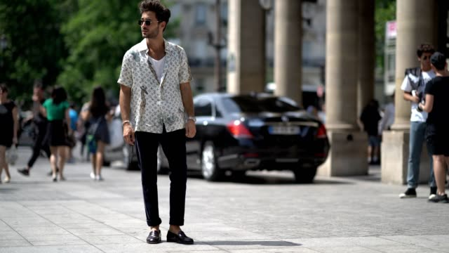 A guest wears a Vuitton shirt outside the Louis Vuitton show during Paris Fashion Week Menswear Spring/Summer 2018 on June 22 2017 in Paris France