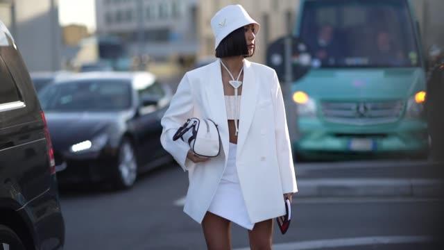 vídeos de stock e filmes b-roll de guest wears a white bob hat, an oversized blazer jacket, a white skirt, sneakers, a bag, white bras, a long necklace, outside prada, during milan... - ténis calçado desportivo