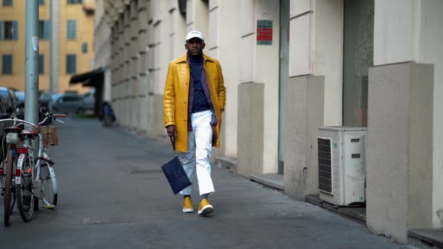 A guest wears a white cap a yellow leather jacket a dark blue clutch white pants yellow sneakers during Milan Menswear Fashion week Fall/Winter...