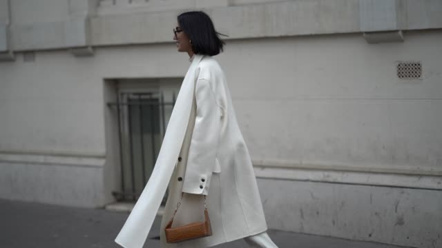 a guest wears a white coat a white top pants shoes a brown leather bag sunglasses outside issey miyake during paris fashion week womenswear... - modewoche stock-videos und b-roll-filmmaterial
