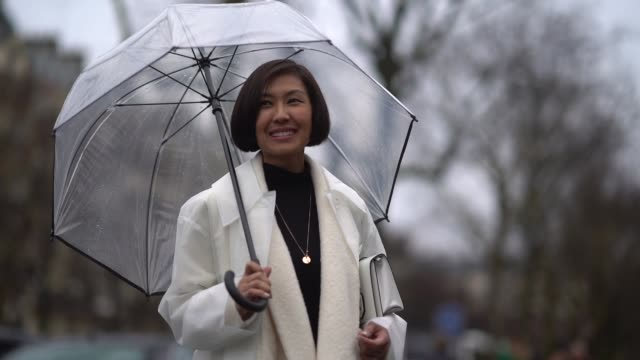 guest wears a white coat, blue jeans, black shoes, holds a transparent umbrella under the rain, during paris fashion week womenswear fall/winter... - guest stock videos & royalty-free footage