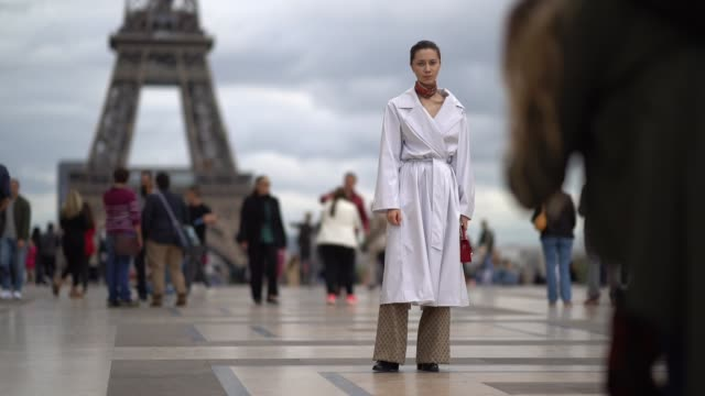 a guest wears a white coat gucci pants outside hermes during paris fashion week womenswear spring/summer 2018 on october 2 2017 in paris france - hermes designer label stock videos and b-roll footage