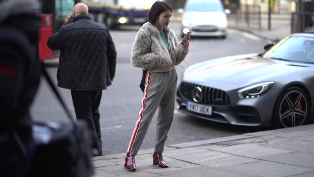 A guest wears a white fur coat striped sportswear pants red shoes during London Fashion Week Men's January 2018 at on January 06 2018 in London...