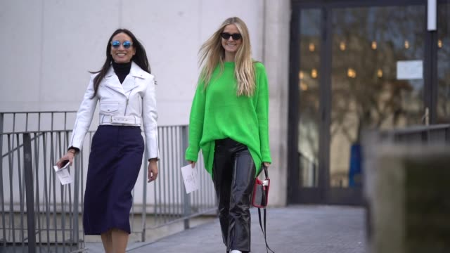 A guest wears a white jacket a blue skirt white shoes a guest wears a green pull over black plastic cropped pants white shoes outside Giambattista...