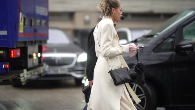 a guest wears a white long coat a black leather crossbody bag pale pink pants pointy shoes during london fashion week fall winter 2020 on february 16... - bag stock videos & royalty-free footage
