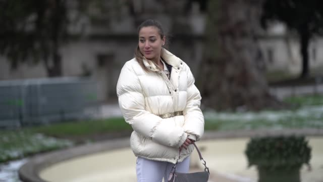 A guest wears a white puffer jacket a Dior Saddle bag white flare pants outside Alexandre Vauthier during Paris Fashion Week Haute Couture Spring...