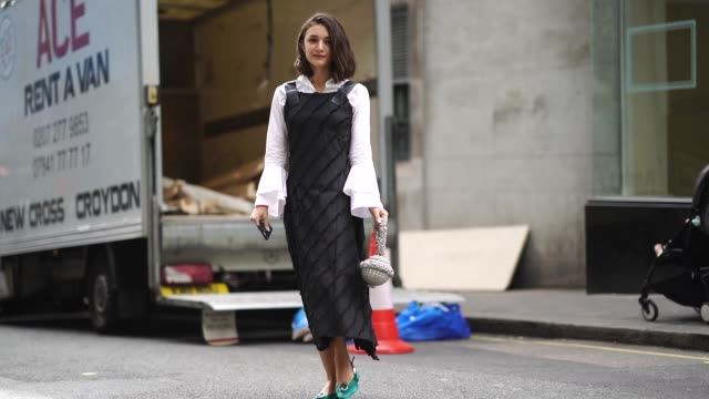 a guest wears a white shirt a black dress a bag shaped as a ball with crystals green shoes during london fashion week september 2018 on september 18... - vestito nero video stock e b–roll
