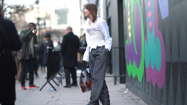 A guest wears a white shirt and a corset during London Fashion Week Men's January 2018 at on January 06 2018 in London England