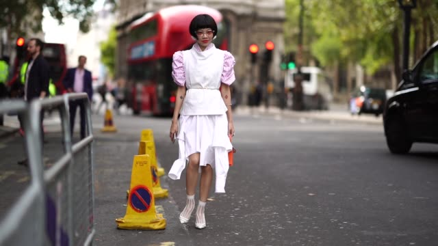 a guest wears a white sleeveless top a pink striped shirt a wite skirt shoes a red bag during london fashion week september 2018 on september 18 2018... - sleeveless top stock videos & royalty-free footage