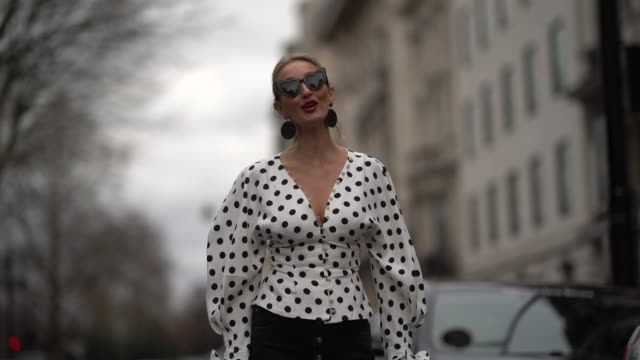 A guest wears a white top with polka dots sunglasses during London Fashion Week February 2018 on February 18 2018 in London England