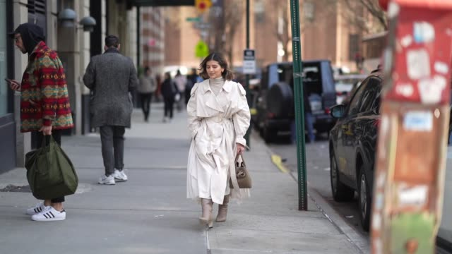 guest wears a white trench coat, a brown bag, pointy boots, a turtleneck pullover, outside bevza, during new york fashion week fall winter 2020, on... - トレンチコート点の映像素材/bロール