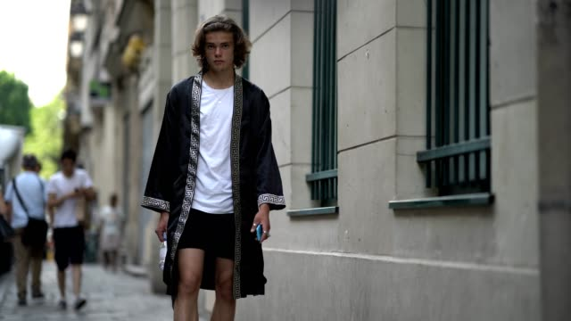 stockvideo's en b-roll-footage met a guest wears a white tshirt a long silk jacket black shorts outside the dries van noten show during paris fashion week menswear spring/summer 2018... - week