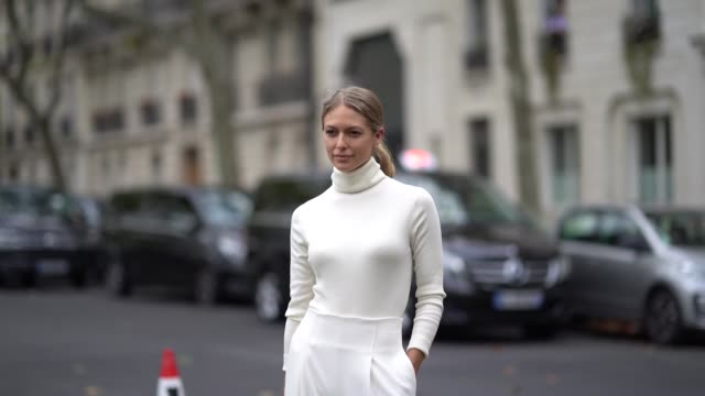 guest wears a white turtleneck pullover, white flare pants, a golden bag, outside valentino, during paris fashion week - womenswear spring summer... - fashion week stock videos & royalty-free footage