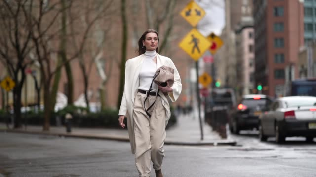 a guest wears a white turtleneck top a white jacket a belt creamcolor pants brown suede shoes a bag during new york fashion week women's fallwinter... - turtleneck stock videos & royalty-free footage