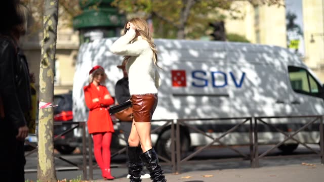 stockvideo's en b-roll-footage met a guest wears a white wool turtleneck pull over sunglasses a short brown leather skirt black boots a long clutch outside miu miu during paris fashion... - coltrui