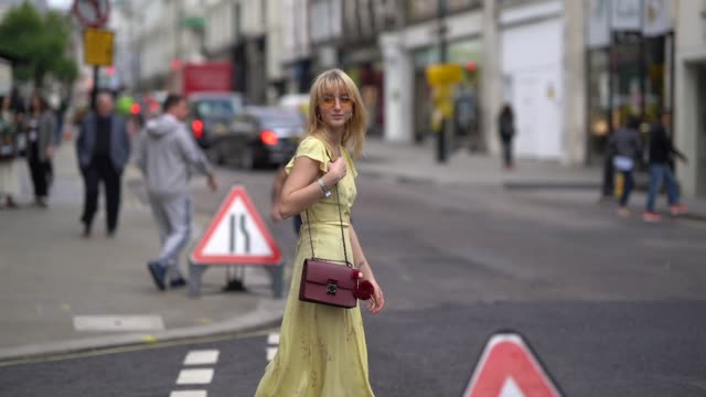 stockvideo's en b-roll-footage met guest wears a yellow dress, during london fashion week september 2017 on september 16, 2017 in london, england. - geel