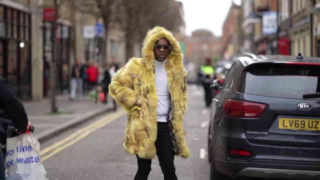 guest wears a yellow fluffy faux fur winter coat with a hood, black pants, leopard print pointy shoes, a turtleneck top, sunglasses, during london... - fluffy stock videos & royalty-free footage