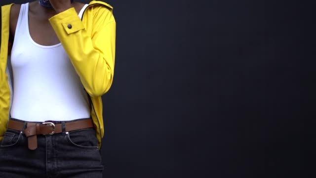a guest wears a yellow jacket a belt a white tank top during london fashion week men's june 2018 on june 08 2018 in london england - coat garment stock videos & royalty-free footage