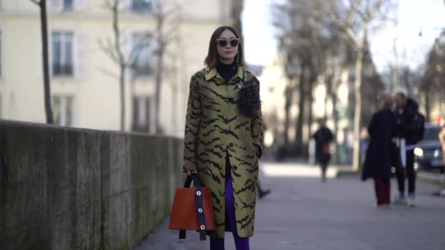 A guest wears a yellow tiger print coat purple boots and an orange bag outside Giambattista Valli during Paris Fashion Week Womenswear Fall/Winter...