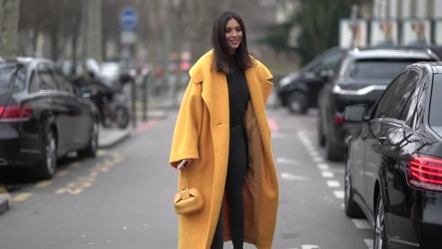 A guest wears an orange coat a bag outside Kenzo during Paris Fashion Week Menswear F/W 20192020 on January 20 2019 in Paris France