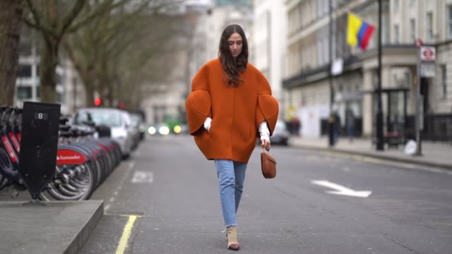 a guest wears an orange coat blue jeans during london fashion week february 2018 on february 18 2018 in london england - london fashion week stock videos and b-roll footage