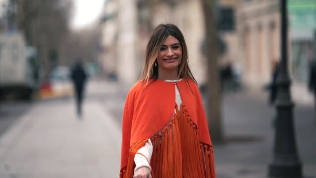 stockvideo's en b-roll-footage met guest wears an orange fringed poncho, outside altuzarra, during paris fashion week womenswear fall/winter 2019/2020, on march 02, 2019 in paris,... - zoom out