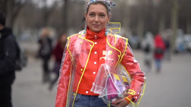 A guest wears an orange jacket a transparent plastic coat cropped jeans blue shoes with pompoms outside Chanel during Paris Fashion Week Womenswear...
