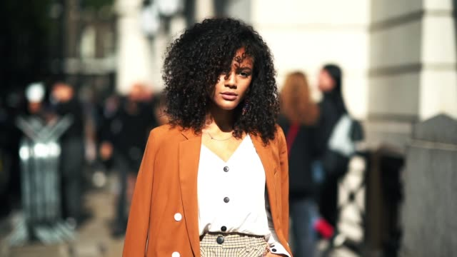 A guest wears an orange jacket a white top flared pants an orange bag during London Fashion Week September 2018 on September 15 2018 in London England