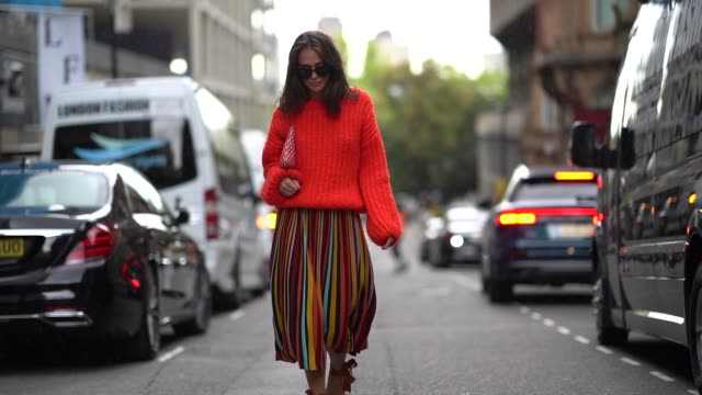vídeos de stock e filmes b-roll de a guest wears an orange pullover a multicolor pleated skirt black shoes sunglasses during london fashion week september 2018 on september 14 2018 in... - saia