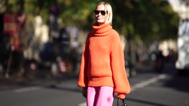 a guest wears an orange pullover pink flare pants a bag during paris fashion week womenswear spring/summer 2019 on september 26 2018 in paris france - pullover stock videos & royalty-free footage