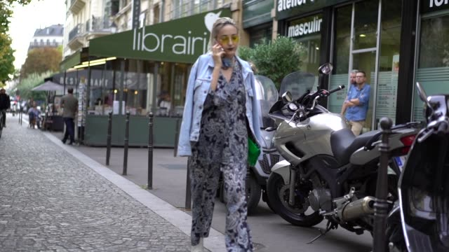 A guest wears an outfit with prints a blue denim jacket outside Koche during Paris Fashion Week Womenswear Spring/Summer 2018 on September 26 2017 in...