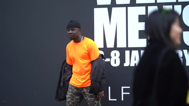 A guest wears black beanie hat orange top black bomber jacket military camouflage pants orange socks black shoes during London Fashion Week Men's...