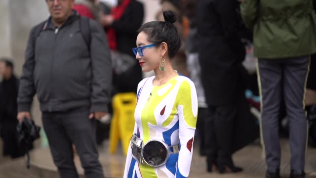 A guest wears blue glasses a multicolor front slit highlow dress a black vinyl belt bag red and transparent vinyl boots during Paris Fashion Week...