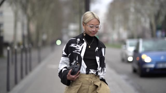 guest wears earrings, a black turtleneck, a white and black shirt, camel suede pants, a navy blue loewe clutch, pointy black shoes, outside nina... - dolcevita video stock e b–roll