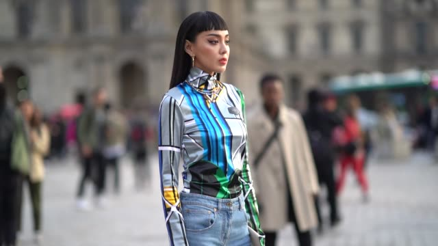 guest wears earrings, a blue gray and green striped turleneck top, blue denim flare pants, white pointy shoes, a white bag, outside louis vuitton,... - dolcevita video stock e b–roll