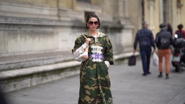 a guest wears earrings a necklace sunglasses a green camouflage dress a light purple trimmed transparent vinyl belt a louis vuitton white bag white... - camouflage stock videos & royalty-free footage