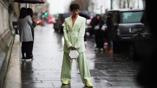 a guest wears earrings a pale green low neck oversized jacket a belt large and flowing pants yellow sneakers a white bag during paris fashion week... - short hair stock videos & royalty-free footage
