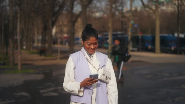 guest wears earrings, a turtleneck pullover, a pale purple sleeveless jacket, a white jacket, white sneakers, a crossbody white quilted chanel bag,... - street style stock videos & royalty-free footage