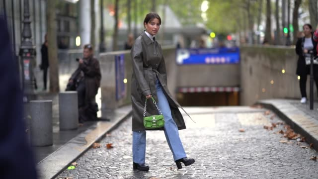 stockvideo's en b-roll-footage met a guest wears earrings a white hineck top a grey leather trench coat blue denim pants black platform boots an applegreen suede bag outside koche... - week