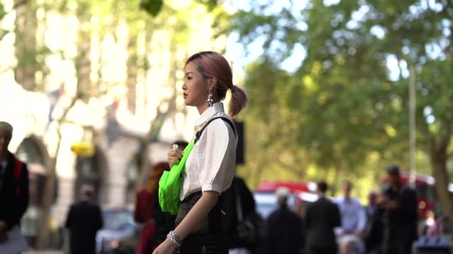 vídeos y material grabado en eventos de stock de guest wears earrings, a white shirt, a neon green bag, during london fashion week september 2019 on september 13, 2019 in london, england. - camiseta