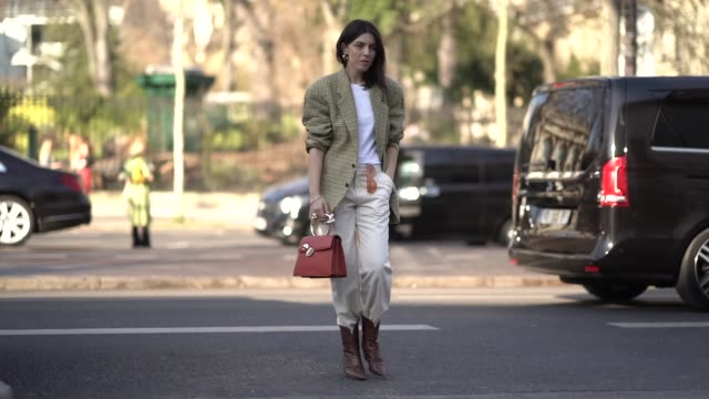 vidéos et rushes de guest wears earrings, a white top, an almond-green checkered oversize jacket, white pants, brown cowboy alligator pattern boots, a gold leather... - bottes