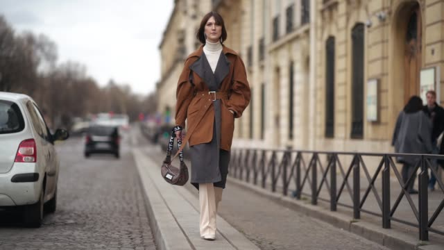 guest wears earrings, a white turtleneck, an orange and brown trench coat, a brown bag,white pants, white shoes, outside y/project, during paris... - dolcevita video stock e b–roll