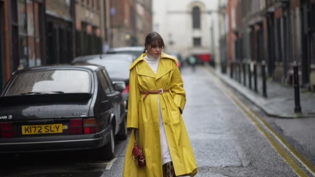 guest wears earrings, a white wool pullover, a white skirt, a belt, a yellow leather trench coat, a chloe bag, leather snake pattern printed boots,... - トレンチコート点の映像素材/bロール