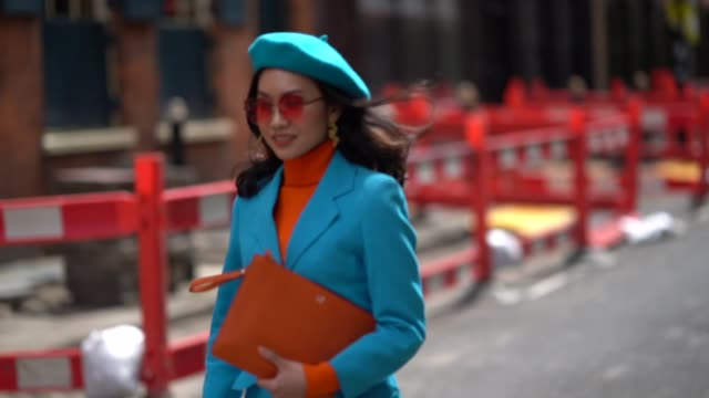 A guest wears earrings an orange turtleneck pullover a blue blazer jacket an orange clutch blue pants blue shoes during London Fashion Week Men's...