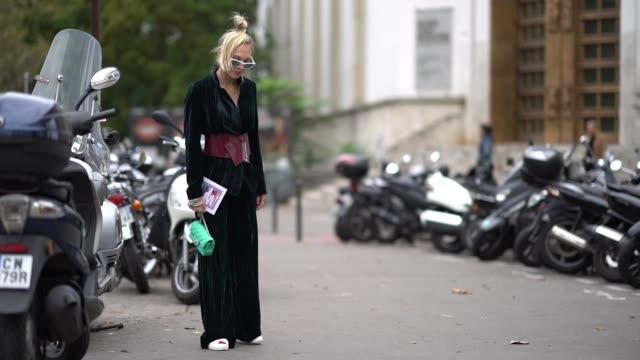 vídeos y material grabado en eventos de stock de a guest wears flare pants and a green chanel bag outside valentin yudashkin during paris fashion week womenswear spring/summer 2018 on october 2 2017... - 2017