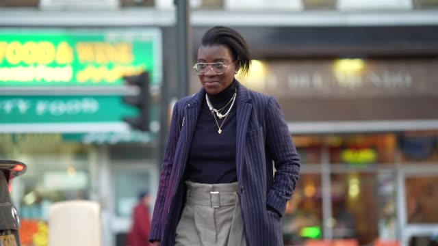 guest wears glasses, a turtleneck pullover, a necklace, a navy blue dark long coat, beige pants, brown leather pointy shoes, earrings, during london... - brown stock videos & royalty-free footage