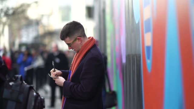 stockvideo's en b-roll-footage met a guest wears glasses an orange scarf a dark blue coat white sneakers shoes during london fashion week men's january 2018 at on january 06 2018 in... - week